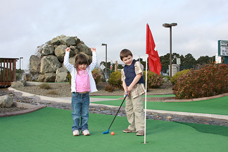 2 young children playing a round of golf at Ed's Mini Golf, located at Emerald Dolphin in Fort Bragg CA